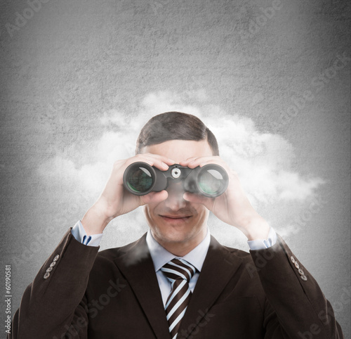 Young businessman looking through binoculars - market research c