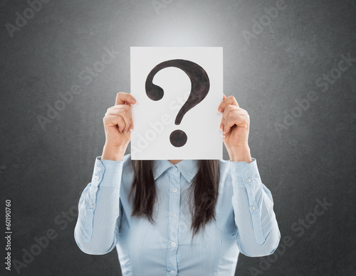 Young woman holding interrogation symbol in front of her face
