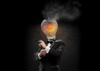 Businessman with exploded overworked lamp head on black backgrou