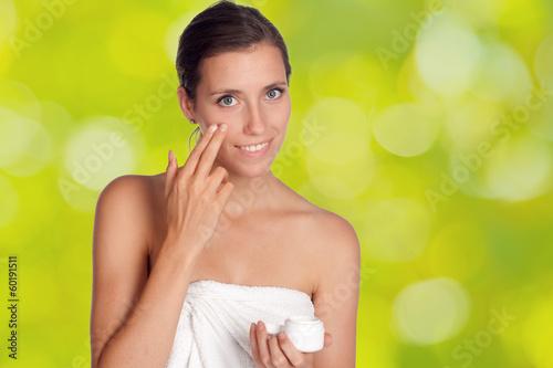 Hübsche junge Frau cremt sich das Gesicht ein