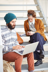 Hipster couple using computer and smartphone outdoors