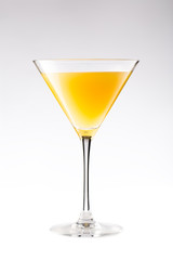 Orange cocktail in a martini glass isolated on white