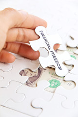 holding a puzzle piece, financial freedom concept