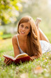 Attractive woman laying on a grass field with a book