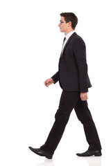 Walking businessman in black suit.