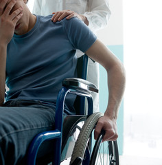 Doctor consoling young man sitting in wheelchair