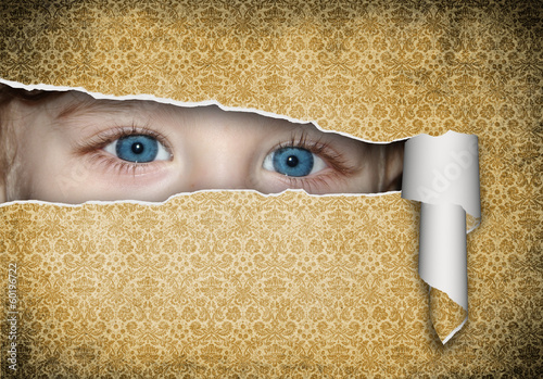 Two children's eyes with a paper hole