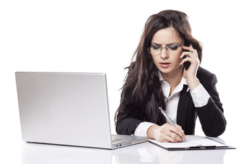 business woman at the desk with a laptop talking on the phone