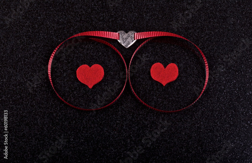 Hearts and red ribbon on ceramic black background
