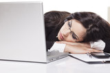 Tired young business woman sleeping on the desk with a laptop