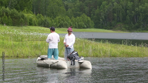 Two men are fishing  from inflatable boat