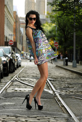 Young brunette standing on old tram rails at Dumbo area