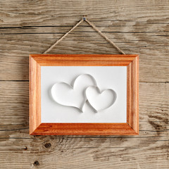 Two hearts in old picture frame hanging on wooden wall