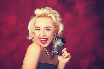 Beautiful blonde women with camera on red background.