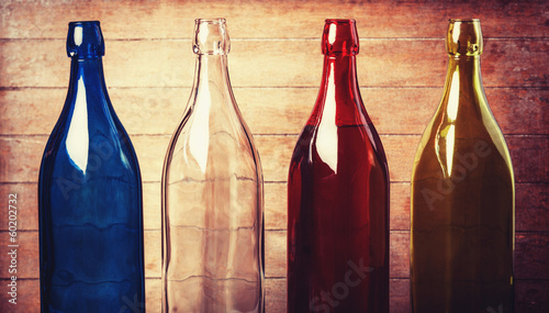 Four empty bottles of wine on wooden background