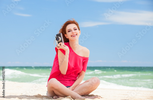 Funny teen girl with camera sitting on the sand at the beach.