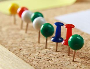 Close up of three push pins.