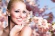 junge blonde Frau vor Kirschblütenhintergrund
