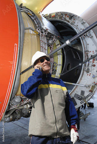 airplane mechanic with large jet-engine in background