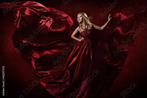 Woman in red waving dress dancing with fluttering flying fabric