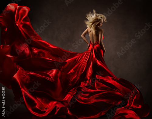 Woman in red waving dress with fluttering flying fabric