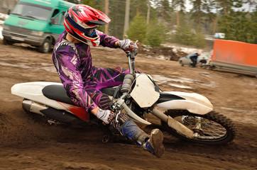 Motocross athlete raised leg forward executes turning