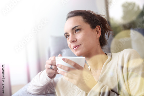 Leinwanddruck Bild Peaceful woman relaxing at home with cup of tea