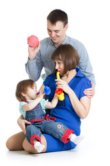 Mother, father and baby girl play musical toys. Isolated on whit