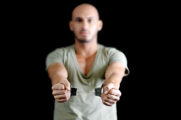 Handcuffs on bald young man, isolated on black