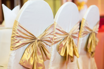 The chairs are decorated with gold bows