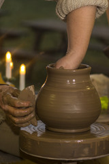 hands of a potter, creating a jar on the circle