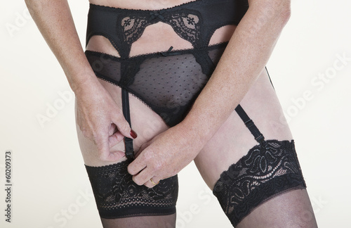 Woman getting dressed fastening stockings