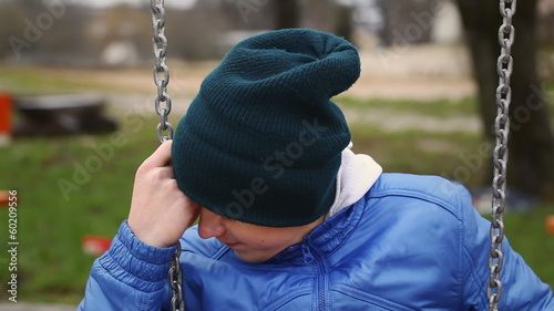 Sorrowful teenage boy swinging in the park episode 2