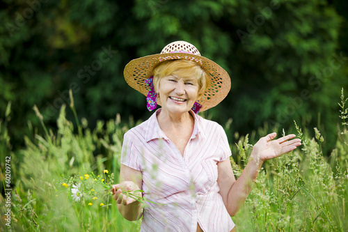Joy. Friendly Mature Woman in Straw Hut with Stretched Arms