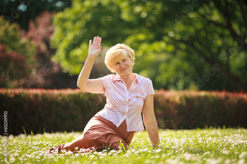 Maturity. White Hair Woman sitting on Grass and having Fun