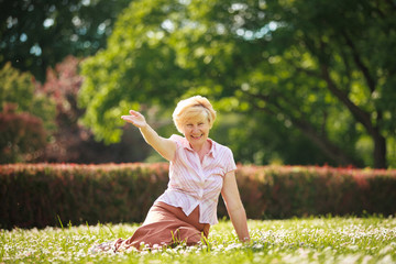 Positive Emotions. Outgoing Old Woman Resting on Grass