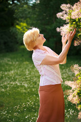 Gardening. Gracious Senior Woman and Flowers