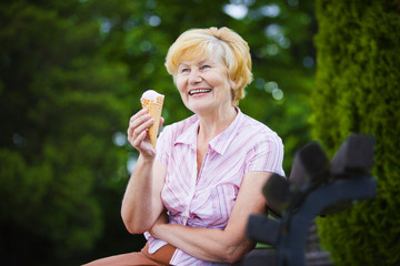 Grey-Haired Woman Relaxing with Ice-Cream on Bench in the Park