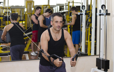 Middle aged man working out with gym equipment