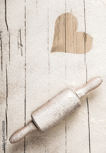 Scattered flour on an old wooden rolling pin