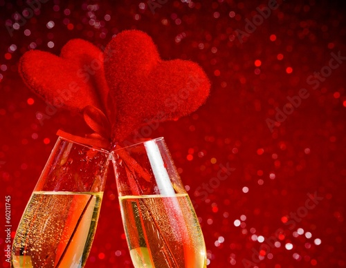champagne flutes with red velvet hearts make cheers on red bokeh
