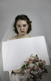 Pretty mad bride holding blank sign