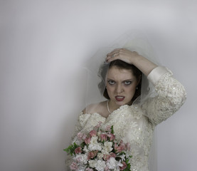 Young bride holds up her veil and makes face
