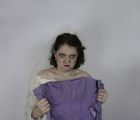 Pretty mad bride holding purple dress