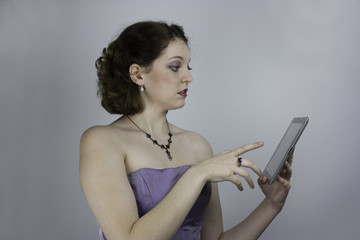 Pretty young woman in purple gown uses tablet
