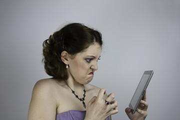 Frustrated young woman wearing purple evening gown uses tablet