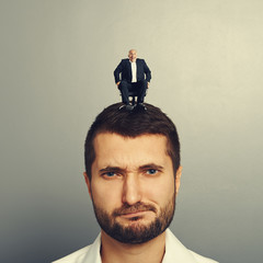 displeased man with small boss on the head