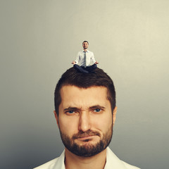 dissatisfied man with small man on the head