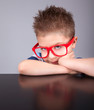 Sad bored five years old boy wearing glasses