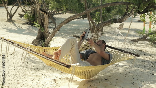 Young man reading news on tablet computer on hammock